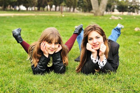 two funny teen girls laying on the green grass  photo