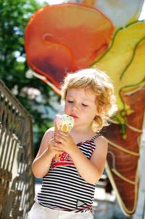 little blonde girl looking with  gladness at the big ice cream Stock Photo - 6813210