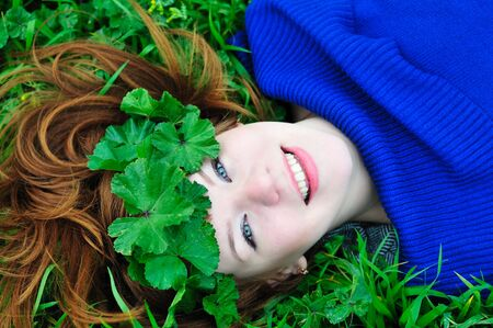 redheaded girl lating on the green grass with crown from leaves photo