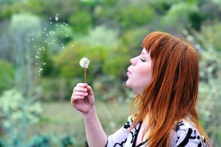 beautiful redheaded teen girl  blowing on dandelion photo