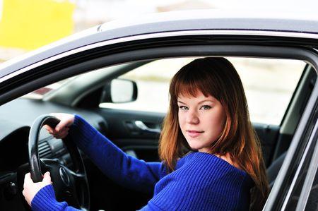 redheaded pretty teen girl  driving a car photo
