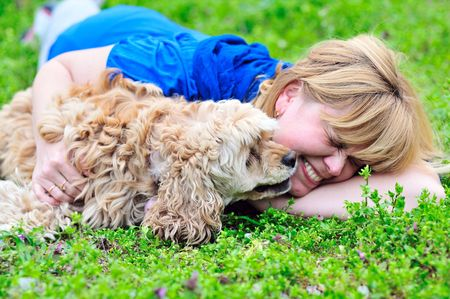 woman and her dog having fun in green grass photo