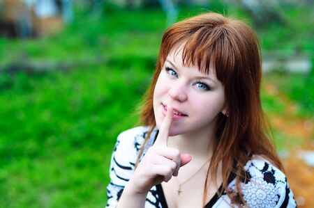 noiseless: redheaded giel asking keep silence outdoors in spring time Stock Photo