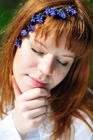 redheaded girl in the spring forest with flowers in her hair