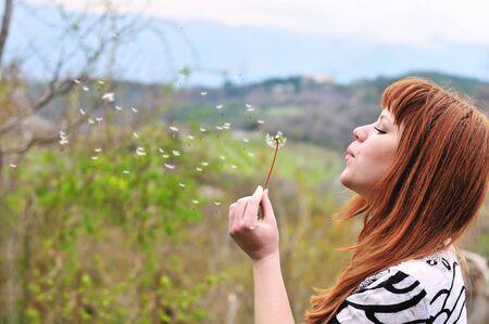 pretty redheaded teen girl blowing on dandelion  photo