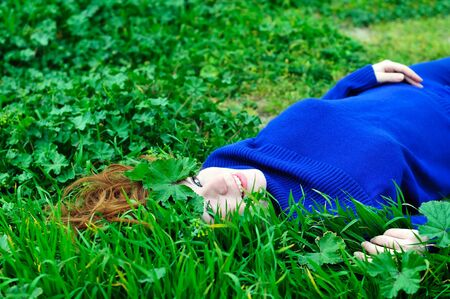 redheaded girl laying on the green grass with crown from leaves  photo