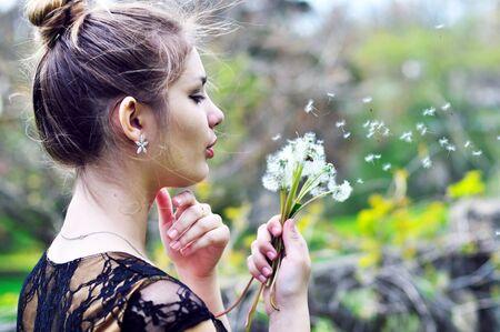 teen pretty girl blowing on many dandelions