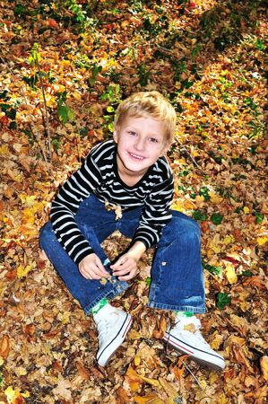 little boy playing with yellow maple leaves in the forest