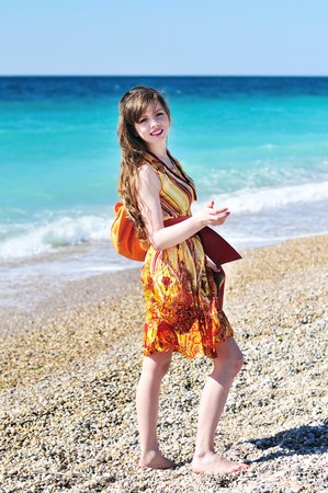 longhaired pretty woman in orange  on the beach photo