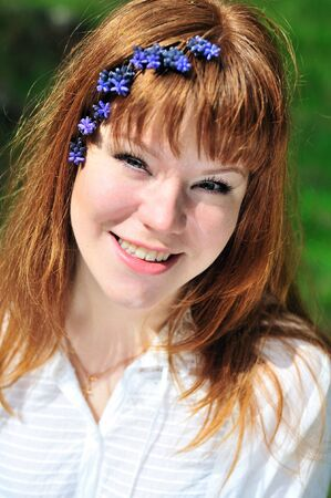 redheaded girl in the spring forest with flowers in her hair  photo