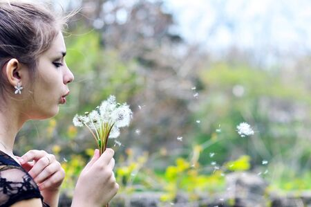 teen pretty girl blowing on many dandelions photo