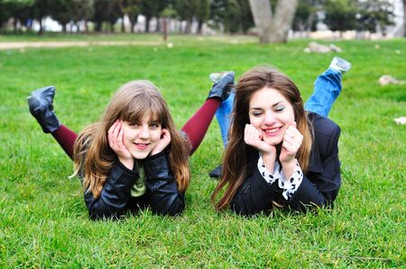 two  laughing  teen girls laying on the green grass  photo