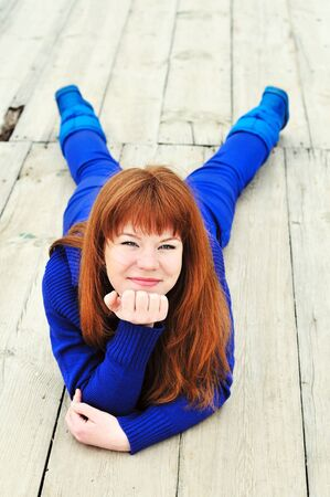 cunning redheaded ten girl laying on the pier  photo
