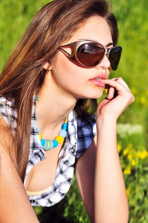 Young pensive beautiful girl on the meadow, wearing sunglasses Stock Photo - 7051527