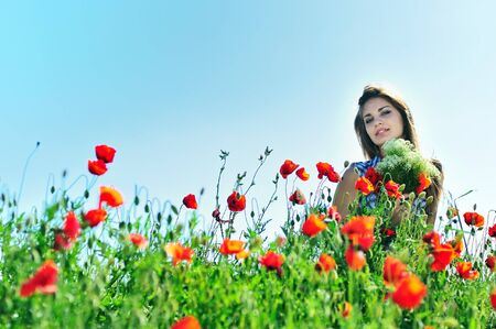 beautiful girl with long hair relaxing in the poppy field  photo