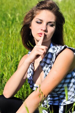 hushed: Young pensive girl with her finger over her mouth in spring time on the meadow