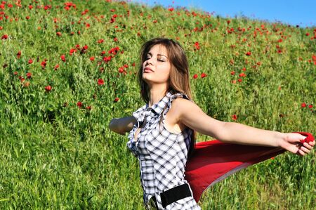 young girl dancing in field and holding  red scarf photo