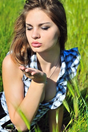 outdoor pursuit: Young tender pretty teen girl blowing a kiss  Stock Photo