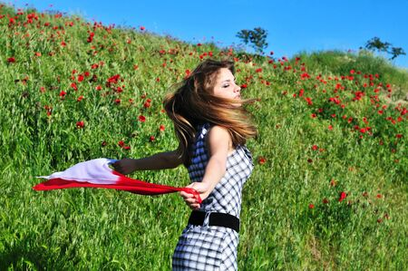 teen girl dancing in field and holding red scarf  photo