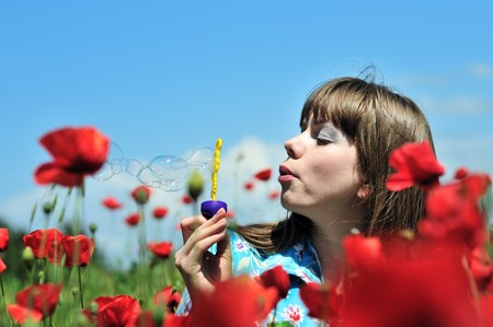young woman blowing soap bubbles on the poppy field photo