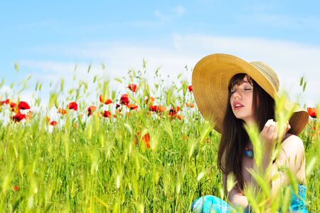 longhaired girl wearing straw hat relaxing in field  photo
