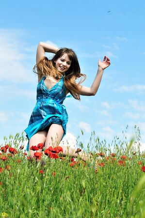 young woman jumping in the poppy field photo