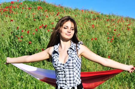 pretty teen girl dancing in field and holding red scarf  photo