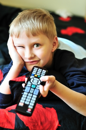 boy watching tv, laying in bad and making face Stock Photo