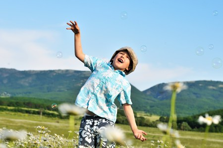 jumping little boy wants to catch soap bubbles Stock Photo - 7138618