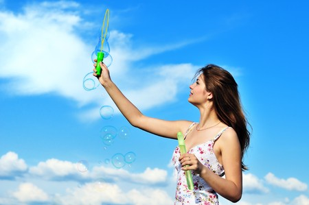 Beautiful young teen girl blowing soap bubbles photo