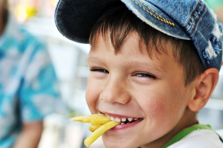 little boy eating french fries in cafe