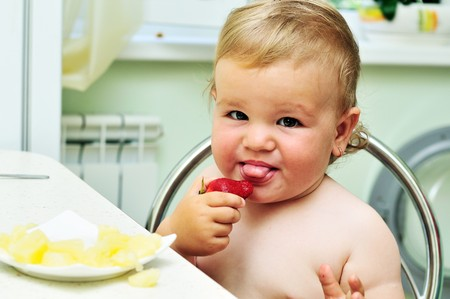 little funny baby girl tasting fresh strawberry photo