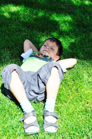 lay down: funny little boy on the sunny meadow
