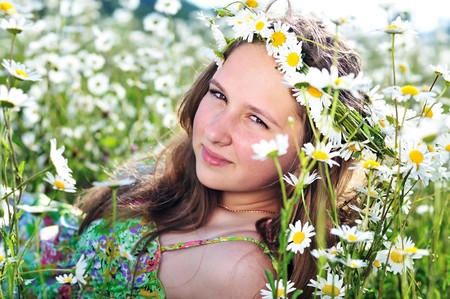beauty spring teen girl with garland from daisies  photo