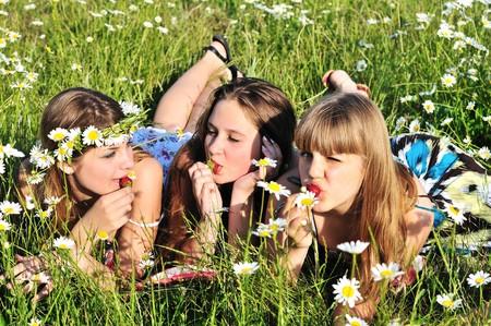 three teen girls enjoying of srtawberry on the daisy field