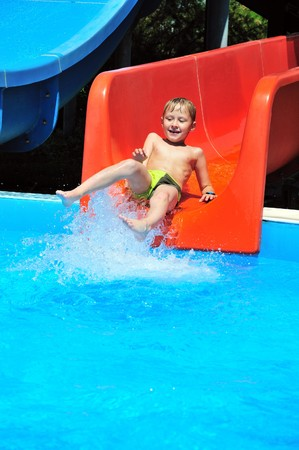 Cute little boy sliding down a water slide photo