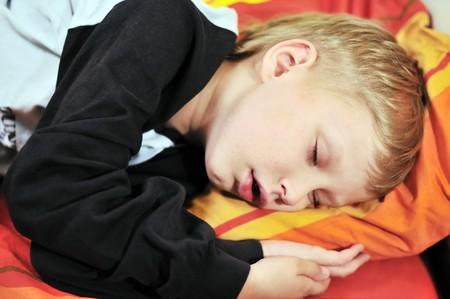 pequeño muchacho Rubio, durmiendo en la cama  Foto de archivo - 7295960