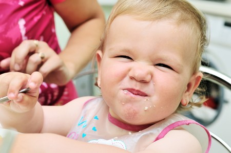 dirty face of funny eating baby girl photo