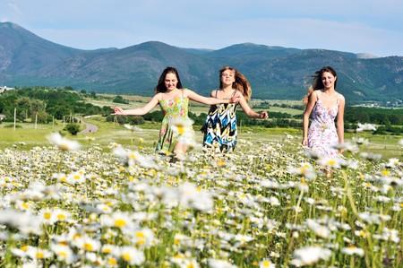 teen happy girls running in daisy field  Stock Photo - 7296083