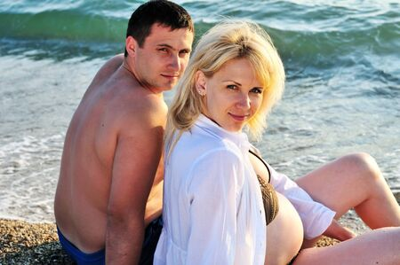 happy husband and pregnant wife near the sea photo