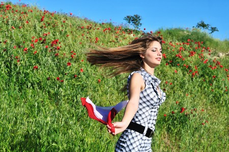 attractive tten girl running in poppy field photo