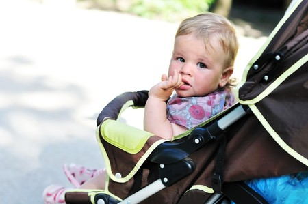 baby girl in the pram licking finger Stock Photo