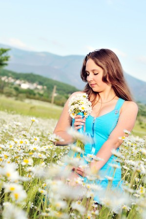 teen girl sitting in daisy field and holding bunch of flowers photo