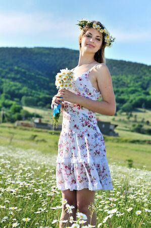 stunning spring lady standing in thr daisy field and holding bunch of flovers photo