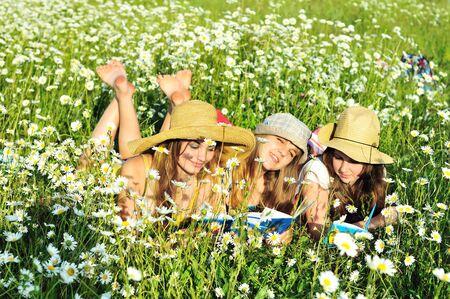 piedi nudi di bambine: tre ragazze a piedi nudi, posa sul campo a Margherita di lettura  Archivio Fotografico