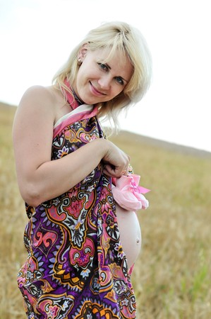 standing pregnant wooman holding pink little booties Stock Photo - 7446622