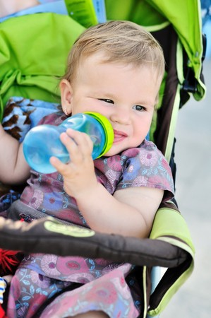 baby girl sitting in the stroller and drinking water photo
