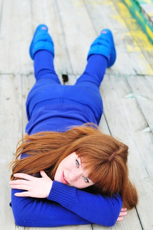 redheaded girl wearing blue clothes laying on the timber floor  photo