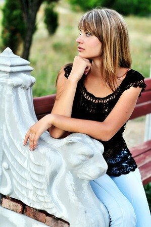 Beautiful tanned girl sitting on the bench  photo