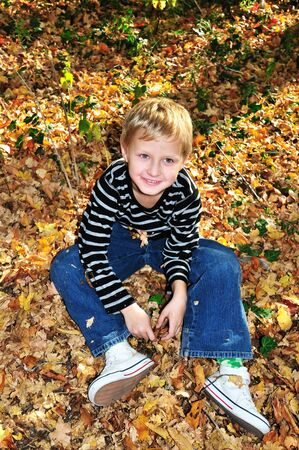 boy sitting on the yellow maple leaves in the forest.  Stock Photo - 7957252